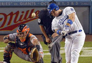 Photo -   Los Angeles Dodgers' A.J. Ellis, right, hits a two-run home run as San Francisco Giants catcher Hector Sanchez catches during the seventh inning of their baseball game, Tuesday, Oct. 2, 2012, in Los Angeles. (AP Photo/Mark J. Terrill)