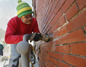 Photo - Larry Lessmann removes old mortar from a wall on a building in downtown Norman Saturday as part of a masonry repair workshop led by preservationist Bob Yapp. PHOTO BY STEVE SISNEY, THE OKLAHOMAN