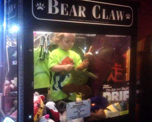 Photo - In this April 14, 2014 photo provided by Rachelle Hildreth, a 3-year-old boy plays with stuffed toys inside a claw crane game machine at a bowling alley in Lincoln, Neb. Police say a 24-year-old woman called 911 Monday afternoon because son was missing from her apartment. Authorities say the toddler was reunited, unharmed, with his mother after employees found him inside the coin-operated game. (AP Photo/Courtesy Rachell Hildreth)