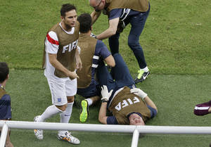 Photo - Frank Lampard, left, walks past as an English staff member grimaces in pain during the group D World Cup soccer match between England and Italy at the Arena da Amazonia in Manaus, Brazil, Saturday, June 14, 2014.  (AP Photo/Themba Hadebe)