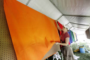 Photo - Assistance League volunteer Kelly Woody sets up a display at this year's May Fair.
