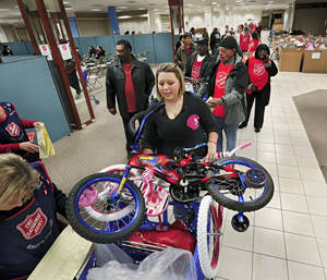 Photo - Salvation Army volunteers distribute toys and bicycles to clients on Thursday at Plaza Mayor at the Crossroads.  Photo by Jim Beckel, The Oklahoman <strong>Jim Beckel - THE OKLAHOMAN</strong>
