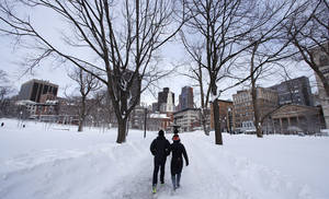 photo - A couple walks through Boston Common in Boston, Saturday, Feb. 9, 2013.  The Boston area received about two feet of snow from a winter storm. A howling storm across the Northeast left the New York-to-Boston corridor shrouded in 1 to 3 feet of snow Saturday, stranding motorists on highways overnight and piling up drifts so high that some homeowners couldn't get their doors open. More than 650,000 homes and businesses were left without electricity. (AP Photo/Charles Krupa)