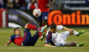 Photo - Chicago Fire midfielder Benji Joya, left, battles for the ball with Real Salt Lake defender Chris Wingert, right, during the first half of an MLS soccer game on Saturday, May 3, 2014, at Toyota Park in Bridgeview, Ill. (AP Photo/Kamil Krzaczynski)
