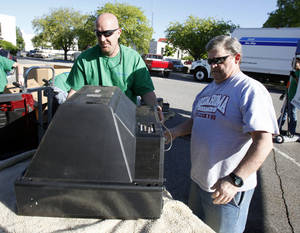 photo - Michael Barton, left, and David Fraser unload a television set during Operation Clean Streets.