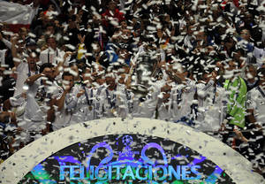 Photo - Real Madrid players are covered in confetti as they hold the Champion League trophy at the end of the Champions League final soccer match between Atletico de Madrid and Real Madrid in Lisbon, Portugal, Saturday, May 24, 2014. (AP Photo/Daniel Ochoa de Olza)