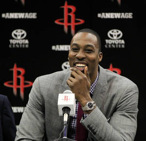 Photo - Houston Rockets' Dwight Howard smiles during a news conference and welcoming ceremony for him to the NBA basketball team, Saturday, July 13, 2013, in Houston. (AP Photo/Houston Chronicle, Karen Warren)  MANDATORY CREDIT