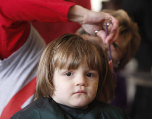 Photo - Two-year-old Destiny Thompson receives a haircut from Michelle Miller-Hayes at last year's ONE DAY event. Archive photo by Paul Hellstern, The Oklahoman.  <strong>PAUL HELLSTERN</strong>