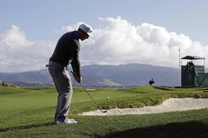 photo - Hunter Mahan chips the ball onto the 17th green of the Pebble Beach Golf Links during the first round of the AT&T Pebble Beach Pro-Am golf tournament  Thursday, Feb. 7, 2013 in Pebble Beach, Calif. (AP Photo/Eric Risberg)