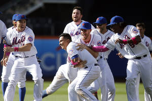Photo - New York Mets' Ruben Tejada, center, gets a hug from Zack Wheeler as he is mobbed by teammates after hitting a game-winning RBI single during the eleventh inning of a baseball game against the Philadelphia Phillies, Sunday, May 11, 2014, in New York.  New York won 5-4 in eleven innings. (AP Photo/Jason DeCrow)