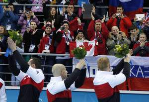 Photo - E.J. Harnden, left, Ryan Fry, center, and Brad Jacobs, acknowledge the fans during the flower ceremony after defeating Britain in the men's curling gold medal game  at the 2014 Winter Olympics, Friday, Feb. 21, 2014, in Sochi, Russia. (AP Photo/Robert F. Bukaty)