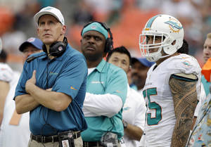Photo - Miami Dolphins head coach Joe Philbin, left, and outside linebacker Koa Misi (55) watch in the final minutes of an NFL football game against the New York Jets, Sunday, Dec. 29, 2013, in Miami Gardens, Fla. The Jets defeated the Dolphins 20-7.  (AP Photo/Lynne Sladky)