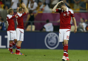 Photo -   Denmark's Nicklas Bendtner, right, walks off the pitch at the end of the Euro 2012 soccer championship Group B match between Denmark and Germany in Lviv, Ukraine, Sunday, June 17, 2012. Denmark lost 1-2. (AP Photo/Frank Augstein)