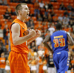 Photo - Oklahoma's Keiton Page (12) reacts after making a basket late in the second half of an NCAA men's college basketball game between the Oklahoma State Cowboys (OSU) and the Tulsa Golden Hurricane (TU), at Gallagher-Iba Arena in Stillwater, Okla., Wednesday, Nov. 30, 2011. Photo by Bryan Terry, The Oklahoman