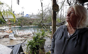 Photo - Dot Peek, looks at the damage Sunday's tornado caused her and her daughter's home next door in Hattiesburg, Miss., Monday, Feb. 11, 2013. The tornado damaged both her roof and that of her daughter's house. Peek said she recently had the swimming pool refinished and now she has two trees in the pool as result from the strong winds that caused damage throughout the South Mississippi college town. (AP Photo/Rogelio V. Solis)