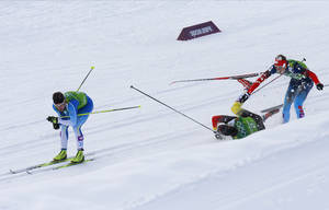 Photo - Germany's Tim Tscharnke, center, falls in front of Russia's Nikita Kriukov, right, after making contact with the skis of Finland's Sami Jauhojaervi, left, in the men's classical-style final of the cross-country team sprint competitions at the 2014 Winter Olympics, Wednesday, Feb. 19, 2014, in Krasnaya Polyana, Russia. (AP Photo/Dmitry Lovetsky)
