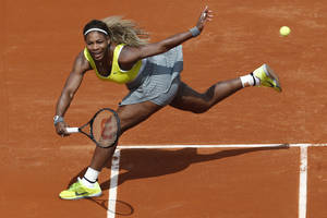Photo - Serena Williams of the U.S. returns the ball during the first round match of the French Open tennis tournament against France's Alize Lim at the Roland Garros stadium, in Paris, France, Sunday, May 25, 2014. (AP Photo/Darko Vojinovic)
