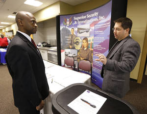 Photo - Jeff Brooks, left, talks with Superior Security Investigations, Inc. Vice President David Welliver during a Job Fair at Rose State College in Midwest City, Friday February  22, 2013. Photo By Steve Gooch, The Oklahoman <strong>Steve Gooch - The Oklahoman</strong>