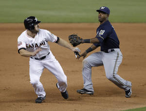 Photo -   Miami Marlins' Bryan Petersen, left, runs from Milwaukee Brewers shortstop Jean Segura as he is caught between second and third bases on a ball hit by Donovan Solano during the seventh inning of a baseball game, Wednesday, Sept. 5, 2012, in Miami. The Brewers defeated the Marlins 8-5. (AP Photo/Wilfredo Lee)