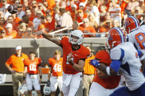 photo -   Oklahoma State quarterback Wes Lunt, left, passes under pressure from Savannah State in the first quarter of an NCAA college football game in Stillwater, Okla., Saturday, Sept. 1, 2012. (AP Photo/Sue Ogrocki)