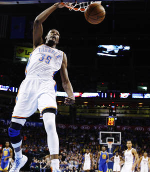 Photo -   Oklahoma City Thunder forward Kevin Durant (35) dunks against the Golden State Warriors in the first quarter of an NBA basketball game in Oklahoma City, Sunday, Nov. 18, 2012. Durant notched his first career triple-double with 25 points, 13 rebounds and a career-high 10 assists. Oklahoma City won 119-109. (AP Photo/Sue Ogrocki)