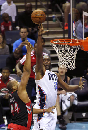 Photo - Charlotte Bobcats center Al Jefferson, right, shoots over Toronto Raptors forward Chuck Hayes in the second half of an NBA basketball game, Monday, Jan. 20, 2014, in Charlotte, N.C. Charlotte won 100-95. (AP Photo/Nell Redmond)