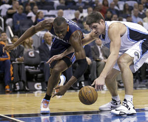 Photo - Charlotte Bobcats' Bismack Biyombo, left, and Orlando Magic's Nikola Vucevic go after a loose ball during the first half of an NBA basketball game, Friday, Jan. 18, 2013, in Orlando, Fla. (AP Photo/John Raoux)