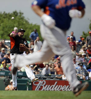 Photo - Miami Marlins' Casey McGehee, left, throws to first base after fielding a ground out by New York Mets' Bartolo Colon, right, in the seventh inning of an exhibition spring training baseball game, Saturday, March 22, 2014, in Jupiter, Fla. (AP Photo/David Goldman)