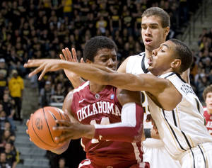 Photo - Oklahoma's Carl Blair, left, is surrounded by Missouri's Phil Pressey, right, and Justin Safford, rear, on Saturday. AP photo