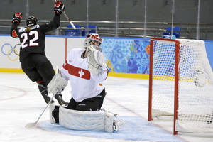 Photo - Goalkeeper Florence Schelling of Switzerland looks back at the puck in the net as Hayley Wickenheiser of Canada celebrates her goal during the second period of the women's ice hockey game at the Shayba Arena during the 2014 Winter Olympics, Saturday, Feb. 8, 2014, in Sochi, Russia. (AP Photo/Matt Slocum)