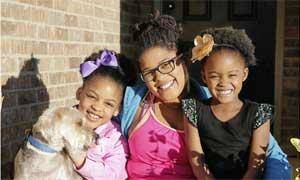 Photo - Nikki Parker, 28, with her two daughters, Layla Parker, 8 (left), and Taylor Parker, 4, with their dog at their home in Broken Arrow. Parker is a success story that is rare among women who become pregnant in their teen years in that she finished her education before age 30 and has worked her way off public assistance. MICHAEL WYKE / Tulsa World