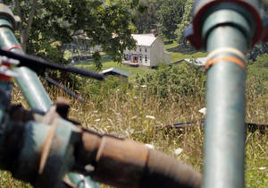 Photo - FILE - This July 27, 2011 file photo shows a farmhouse in the background framed by pipes connecting pumps where the hydraulic fracturing process in the Marcellus Shale layer to release natural gas was underway at a Range Resources site in Claysville, Pa. In Pennsylvania's fracking boom, new and more unconventional wells leaked far more than older and traditional wells, according to a study of inspections of more than 41,000 wells drilled. And that means that that methane leaks could be a problem for drilling across the nation, said the author of the study, which funded in part by environmental activist groups and criticized by the energy industry. The study was published Monday by the Proceedings of the National Academy of Sciences. (AP Photo/Keith Srakocic, File)