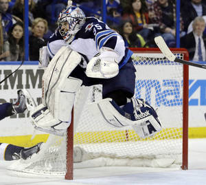 Photo - Winnipeg Jets goalie Al Montoya leaps into the air to avoid a sliding St. Louis Blues player during the second period of an NHL hockey game Saturday, Feb. 8, 2014, in St. Louis. (AP Photo/Jeff Roberson)