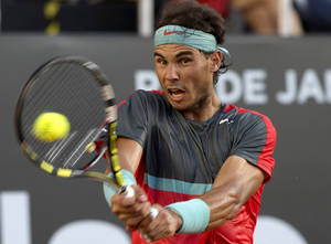 Photo - Rafael Nadal, of Spain, returns the ball to Alexandr Dolgopolov, of Ukraine, during their final game at the Rio Open tennis tournament in Rio de Janeiro, Brazil, Sunday, Feb. 23, 2014. (AP Photo/Silvia Izquierdo)