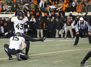 Photo - Baylor kicker Aaron Jones (43) kicks a field goal against Oklahoma State in the second quarter of an NCAA college football game in Stillwater, Okla., Saturday, Nov. 23, 2013. Baylor's Brody Trahan (15) holds. (AP Photo/Sue Ogrocki)