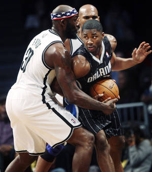 Photo - Orlando Magic's E'Twaun Moore, right, fights with Brooklyn Nets' Reggie Evans for the ball during the first half of an NBA basketball game in New York, Sunday, Nov. 11, 2012.  (AP Photo/Seth Wenig) ORG XMIT: NYSW102