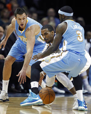 Photo - Memphis Grizzlies guard Mike Conley is trapped between Denver Nuggets forward Danilo Gallinari, left, of Italy, and guard Ty Lawson (3) in the first half of an NBA basketball game on Saturday, Dec. 29, 2012, in Memphis, Tenn. (AP Photo/Lance Murphey)