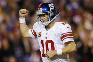 Photo - New York Giants quarterback Eli Manning celebrates a touchdown pass to tight end Martellus Bennett during the first half of an NFL football game against the Washington Redskins in Landover, Md., Monday, Dec. 3, 2012. (AP Photo/Patrick Semansky)