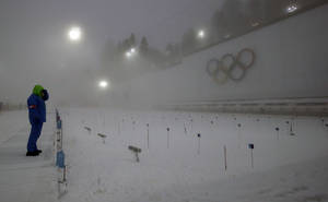 Photo - A race officer checks visibility from the shooting range, prior to the men's biathlon 15k mass-start, at the 2014 Winter Olympics, Tuesday, Feb. 18, 2014, in Krasnaya Polyana, Russia. (AP Photo/Lee Jin-man)