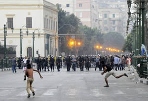 Photo -   Egyptian protesters hurl stones at riot police in downtown Cairo, Egypt, early Saturday, Sept. 15, 2012, before police cleared the area after days of protests against a film ridiculing the Prophet Muhammad. Egyptian police on Saturday cleared out protesters who have been clashing with security forces for the past four days near the U.S. Embassy as most cities around the Muslim world reported calm a day after at least six people were killed in a wave of angry protests over an anti-Islam film.(AP Photo)