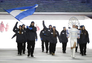 Photo - Cristian Simari Birkner of Argentina carries the national flag as he leads the team during the opening ceremony of the 2014 Winter Olympics in Sochi, Russia, Friday, Feb. 7, 2014. (AP Photo/Mark Humphrey)