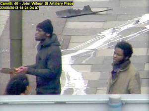 Photo - In this photo made from CCTV and released by the Metropolitan Police on Tuesday, Dec. 3, 2013,  Michael Adebolajo and Michael Adebowale  speak to a member of the public near to the Woolwich Barracks in London in May 2013. The footage was shown in court during the trial of Michael Adebolajo, 28, and Michael Adebowale, 22, who stand accused of the murder of Fusilier Lee Rigby. Rigby of the Royal Regiment of Fusiliers, was attacked and killed by two men near the barracks. Two men ran him down with a car, then used knives and a cleaver to stab and hack him to death.  (AP Photo / Metropolitan Police)   UNITED KINGDOM OUT NO SALES NO ARCHIVE