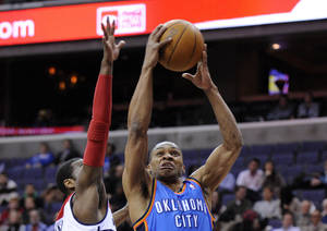 photo - Oklahoma City Thunder guard Russell Westbrook (0) goes to the basket against Washington Wizards guard John Wall, left, during the first half of an NBA basketball game on Wednesday, Jan. 18, 2012, in Washington. (AP Photo/Nick Wass) ORG XMIT: VZN104