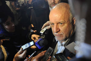 Photo - Iran's Minister of Petroleum Bijan Namdar Zangeneh talks ro journalists as he arrives at a hotel in Vienna, Austria, on Tuesday, Dec. 3, 2013. The Organization of Petroleum Exporting Countries, OPEC, will meet on Wednesday to decide on the cartel's oil output against a backdrop of slowing crude demand and unrest in member nation Libya. (AP Photo/Hans Punz)
