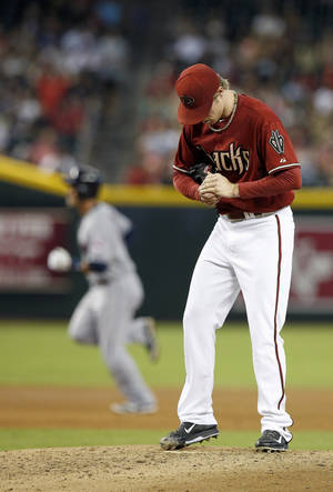 Photo - Arizona Diamondbacks' Chase Anderson, right, rubs up a new baseball as Cleveland Indians' Yan Gomes rounds the bases after hitting a home run during the second inning of a baseball game Wednesday, June 25, 2014, in Phoenix. (AP Photo/Ross D. Franklin)