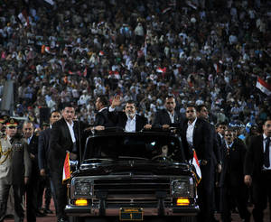 Photo -   In this image released by the Egyptian Presidency taken on Saturday, Oct. 6, 2012, Egyptian President Mohammed Morsi, waves to the crowd gathered in a stadium upon his arrival for a speech on the 6th of October national holiday marking the 1973 war with Israel in Cairo, Egypt. Morsi boasts of his achievements in his first 100 days in office but sidesteps the key issues in the political transition to democratic rule. (AP Photo/Egyptian Presidency)