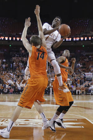 Photo - Texas' Isaiah Taylor (1) crashes into Oklahoma State's Marek Soucek (14) as he drives to the basket during the first half on an NCAA college basketball game, Tuesday, Feb. 11, 2014, in Austin, Texas. (AP Photo/Eric Gay)