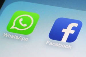 Photo - This Wednesday, Feb. 19, 2014 photo shows the WhatsApp and Facebook app icons on an iPhone in New York. On Wednesday the world's biggest social networking company, Facebook, announced it is buying mobile messaging service WhatsApp for up to $19 billion in cash and stock. (AP Photo/Patrick Sison)