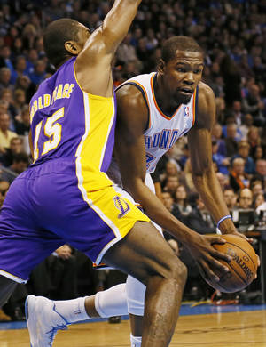 Photo - Oklahoma City's Kevin Durant (35) works against Los Angeles' Metta World Peace (15) during an NBA basketball game between the Oklahoma City Thunder and the Los Angeles Lakers at Chesapeake Energy Arena in Oklahoma City, Friday, Dec. 7, 2012. Photo by Nate Billings, The Oklahoman