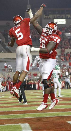 Photo -   Houston running back Charles Sims, left, celebrates his touchdown run with offensive lineman Jacolby Ashworth during the second quarter of an NCAA college football game against North Texas, Saturday, Oct. 6, 2012, in Houston. (AP Photo/Houston Chronicle, Nick de la Torre)